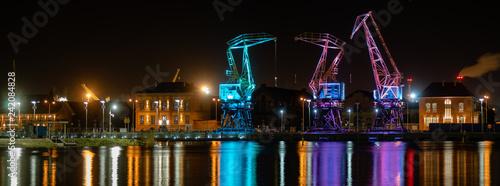 Fotografie, Obraz Szczecin,Poland-December 2018:Illuminated old port cranes on a boulevard in Szczecin City at night
