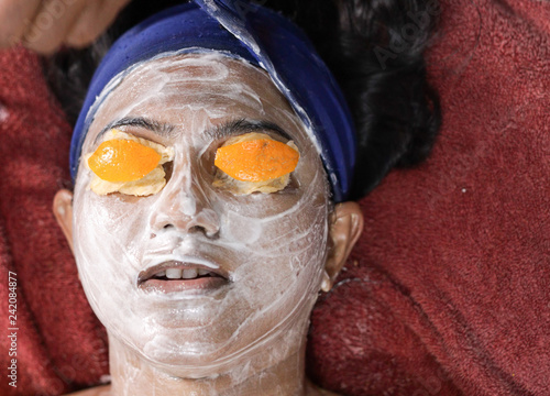 Fotografie, Obraz  facial pack mask applied on face of a lady with hair band with eyes closed with orange peel