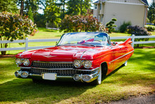 Front Of A Red Cadillac De Ville At Sunset Sitting On Grass