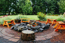 Benches Sitting Around A Campfire With Rocks And Wood