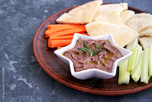 Fototapeta Red bean dip with baked garlic, thyme and olive oil in a star bowl. Served with chopped raw carrots, celery and pita pieces. obraz