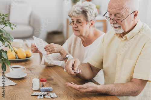 Fotografia  Senior couple sitting at the table and taking medicines