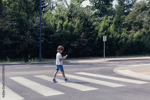 Fotografija Boy crossing the street while looking at his smartphone