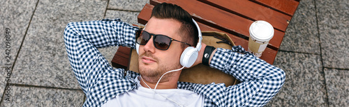 Photo sur Toile Magasin de musique Young man with headphones lying on a park bench outdoors