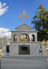 Typowy Nagrobek Z Białego Marmuru, Z Krzyżem I Dwoma Aniołami Po Bokach, Z Tyłu, Na Cypryjskim Cmentarzu, W Tle Rozmyte Inne Nagrobki, Drzewo, Błekitne Niebo