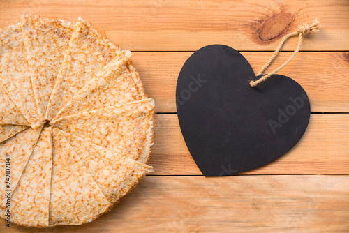 Top view of crepes (french pancakes), blank heart with copy space, rustic wood background