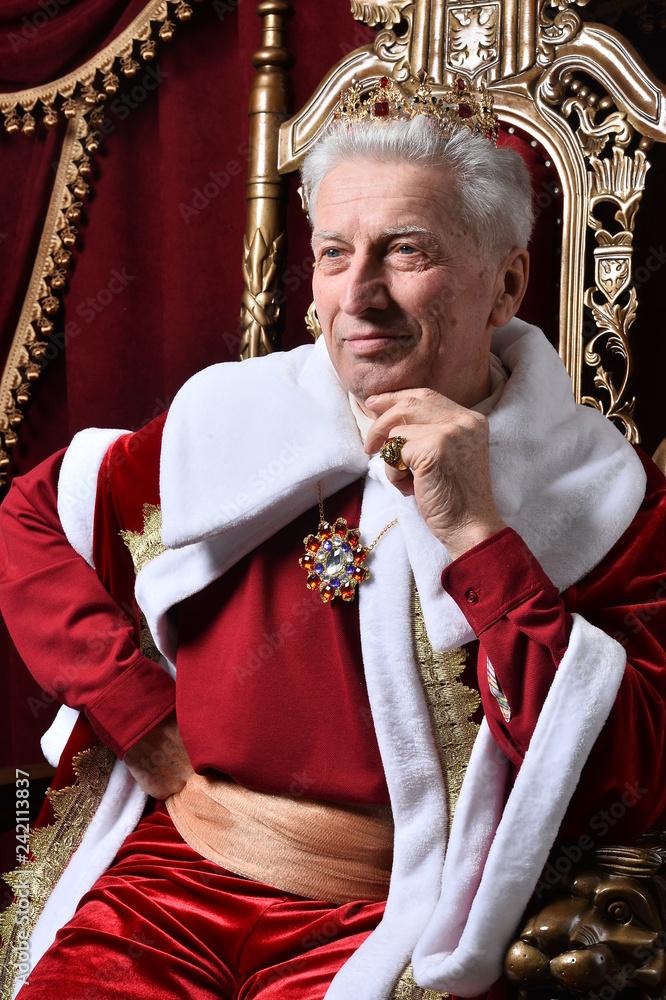 Fototapeta Portrait of confident senior man in red cloak