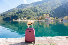 Pink Suitcase With Straw Hat On Sea Beach. Concept Of Travel, Vacation, Female Tourism, Trip, Adventure. Nature Background Of Amazing View With Blue Lake, Mountains, Autumn Landscape.