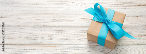 Fotografía Beautiful gift box with a blue bow on the white wooden table