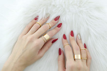 Woman Hands With Red Nail Art And Jewelry On Fur Background.