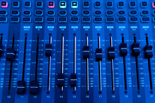 Professional Audio Studio Sound Mixer Console Board Panel With Recording , Faders And Adjusting Knobs,TV Equipment. Blue Tone And Close-up Image.