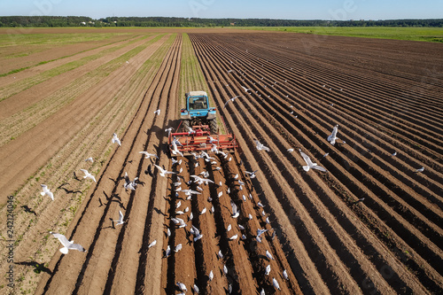 Foto  Agricultural work on a tractor farmer sows grain