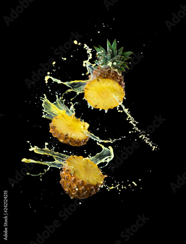 Slice of yellow pineapple with splashing pineapple juice isolated on black background