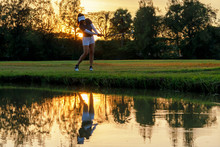 Healthy Sport. Asian Sporty Woman Golfer Player Chips And Swing Golf On The Green Sunset Evening Time, She Presumably Does Exercise.  Healthy Lifestyle Concept.