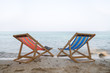 The orange and blue beach chair are on the clear sand beach with sea in background