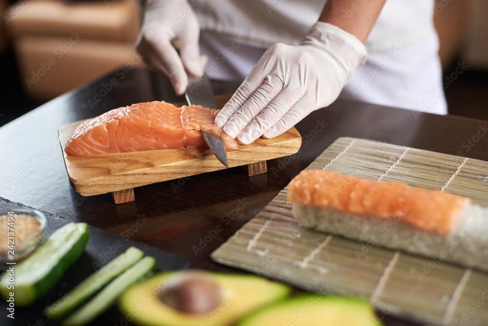 Fototapety, obrazy: Close-up view of process of preparing delicious rolling sushi in restaurant. Female hands in disposable gloves slicing salmon.