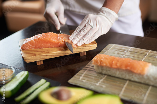 Fototapeta Close-up view of process of preparing delicious rolling sushi in restaurant. Female hands in disposable gloves slicing salmon. obraz