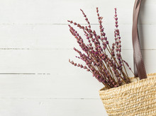 Straw Handwoven Beach Shoulder Bag With Leather Handles Lavender Flowers Bouquet On White Plank Wood Background. Provence Mediterranean Rural Style Interior. Natural Materials