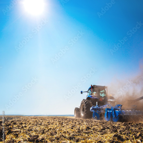 Photo  The tractor plows the field, cultivates the soil for sowing grain