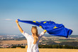canvas print picture - Woman holding waving european union flag outdoors