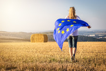 Woman Running With Waving European Union Flag In Countryside
