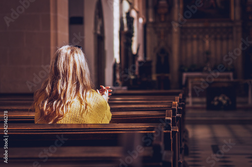Obraz Young woman praying and meditating in church - fototapety do salonu