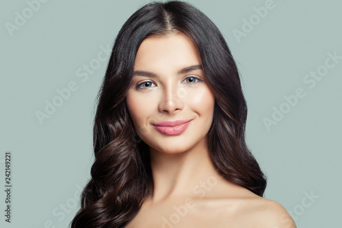 Fotografie, Obraz  Happy woman brunette with long wavy hair on blue background
