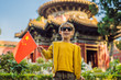 Enjoying vacation in China. Young boy with national chinese flag in Forbidden City. Travel to China with kids concept. Visa free transit 72 hours, 144 hours in China