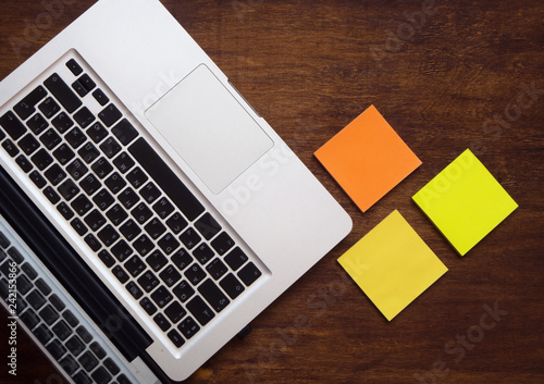 Fotografía  Top view of workplace with open laptop and stickers on wooden background