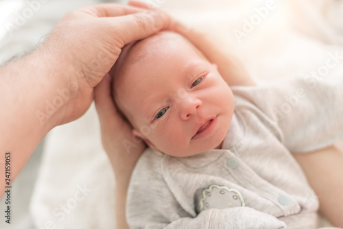 Baby in the hands of mom and dad close up. Canvas Print