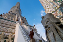 Close Up Picture Of A Chinese Guardian Statue With The Wat Arun In The Background
