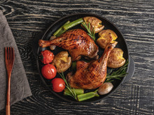 Roasted Duck Legs With Potatoes,tomato In A Frying Pan , Black Surface, Close Up