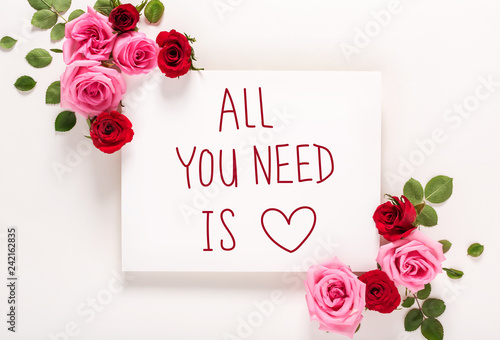Photo  All You Need Is Love message with roses and leaves top view flat lay