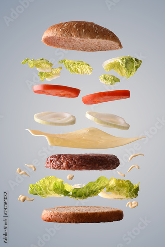 Classic beef burger with onion floating on gray background