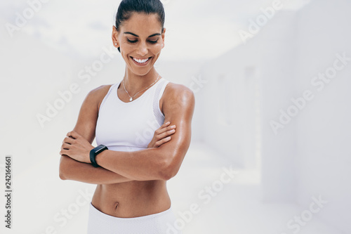 Photo Smiling fitness woman standing with arms crossed