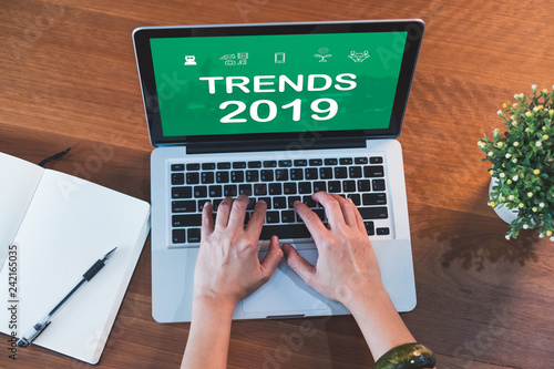 Fotografía  top view hand type trends 2019 on laptop keyboard with open notebook and plant on table at home