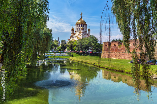 Foto  Nice scenario with a tall church and a lake with trees around in Romania
