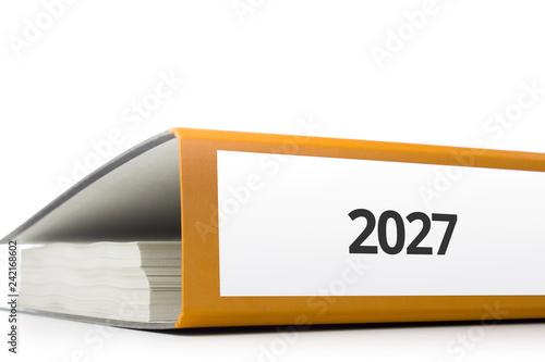 Photo  oranger Aktenordner gefüllt mit Papierseiten und Beschriftung 2027 liegend vor w