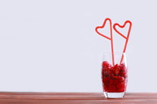 Glass With Frozen Raspberry On The Wood Table And Two Red Tubes With A Shape Of Heart.