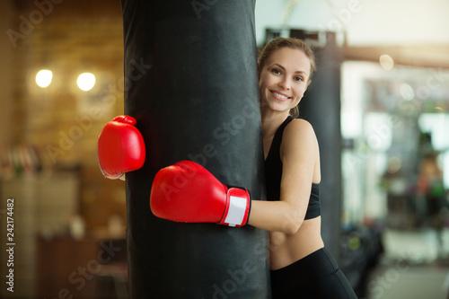 Fotografía  beautiful young girl hugs a punching bag in the gym