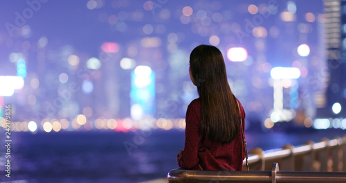 Woman look arond and far away in the city at night