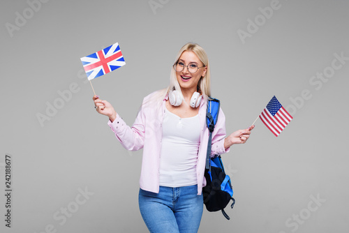 Fotografía  Education, foreign language translator, english, student - smiling blond woman in headphones holding American and British flags