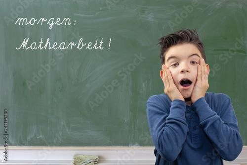 Fotografía  Kind vor Schultafel zeigt Erschrecken vor Mathearbeit