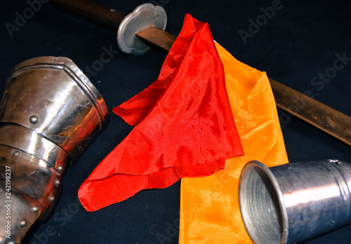 Photo  Saber, knight glove, Cup with colored flags on a black background
