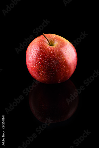 Fotografia, Obraz  Ripe red apple with water drops on a black background with refle