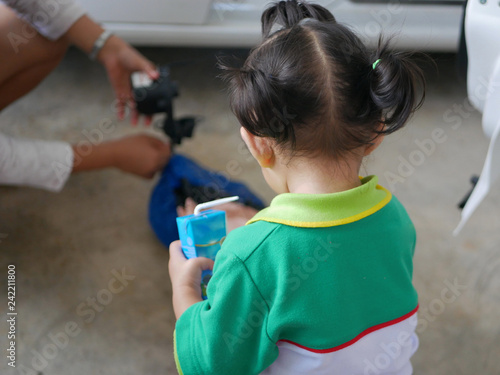 Fotografía  Little Asian baby girl interested in her mother pumping air into a rocking doll