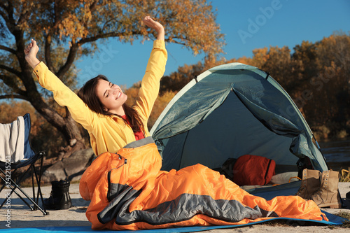 Woman waking up in sleeping bag near tent outdoors