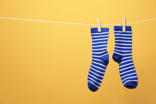 Cute Socks On Laundry Line Against Color Background. Space For Text
