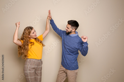 Fotografía  Happy young people celebrating victory on color background