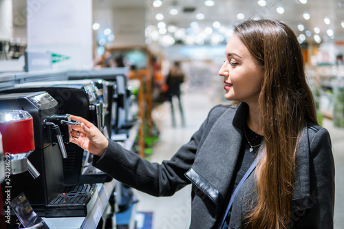 Obraz na plátně Smart modern female customer choosing coffee machine at electronics store